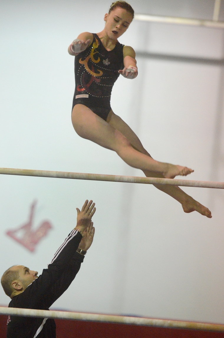 Hamilton. Ontario, Tuesday, January 21,2014 - Gymnast Maegan Chant, who trains at World Class gymnastics, has her sights set on the Olympics inn 2016. Maegan gets a helping hand from coach Gabriel Tantaru on the bars. Photo by: Barry Gray, The Hamilton Spectator.