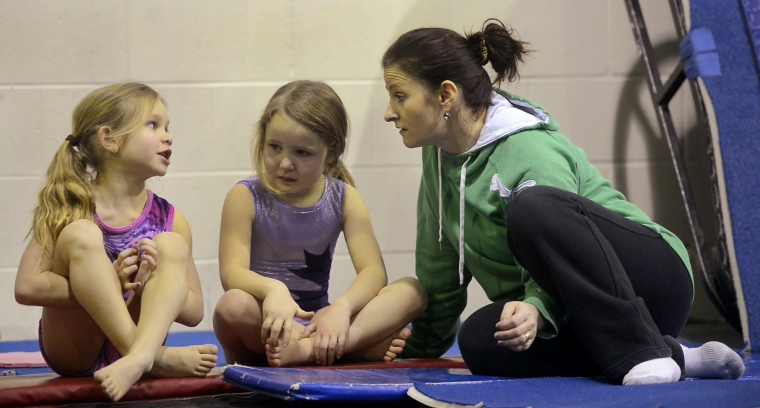 Hamilton. Ontario, Tuesday, January 21,2014 - Gymnast Maegan Chant, who trains at World Class gymnastics, has her sights set on the Olympics inn 2016. Maegan waits her turn to practice a technique. Coach Cristina Bontas-Tantaru chats with a couple of young gymnasts. Photo by: Barry Gray, The Hamilton Spectator.